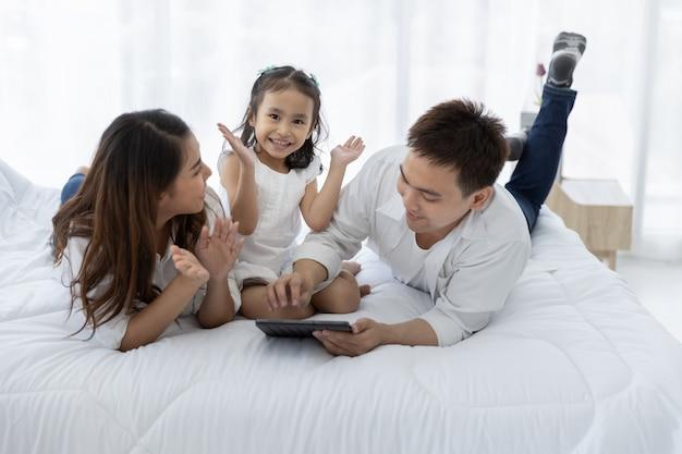 デジタルタブレットを持つアジアの家族 Premium写真