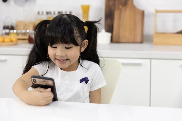 幸せなアジアの女の子は、スマートフォンを楽しむ Premium写真