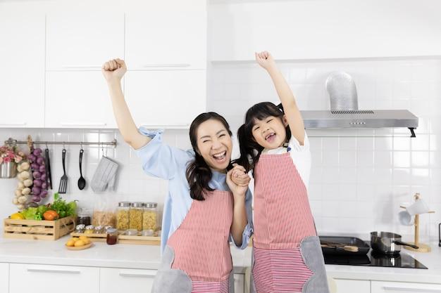 台所でエプロンを着ているアジアの家族の肖像画 Premium写真