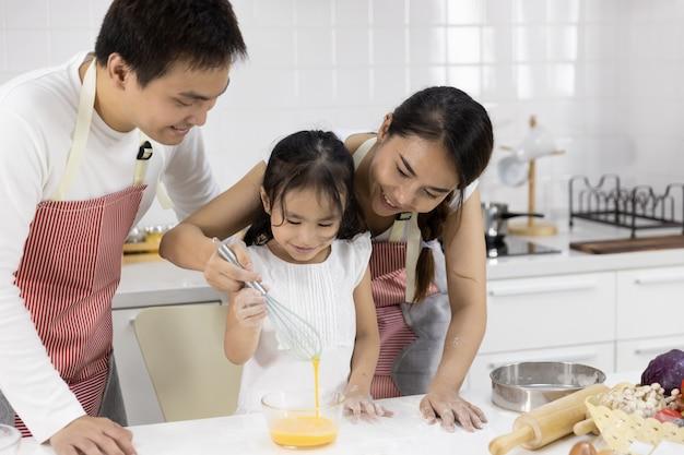 Семья взбивать яйца в миске Premium Фотографии