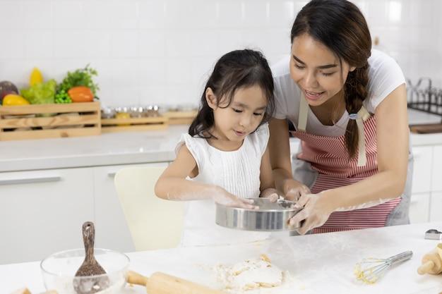 Мать и дочь готовят тесто Premium Фотографии