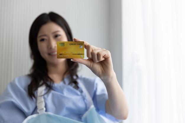 Счастливая азиатская девушка на больничной койке с кредитной картой Premium Фотографии