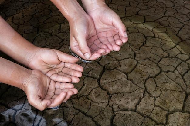 乾燥した土壌での子供たちの手。 Premium写真