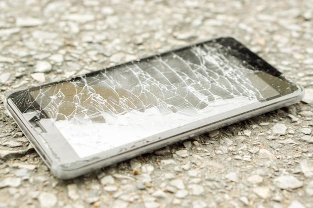 クローズアップ黒携帯電話の事故は道路と自然の太陽光で壊れたガラスに落ちる。 Premium写真