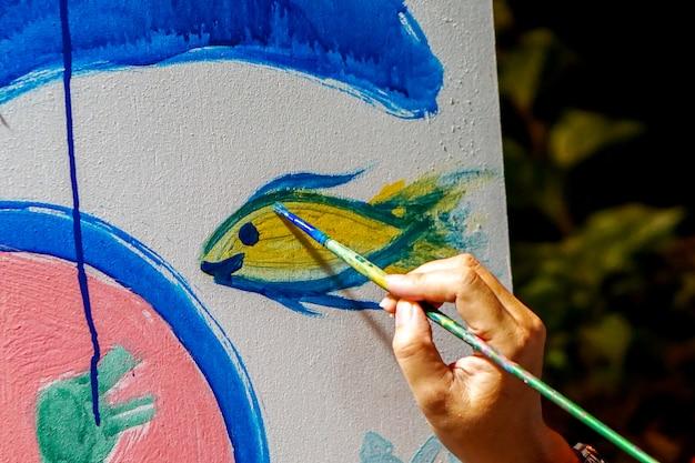 ブラシを保持している美術学生のクローズアップ手は、新しい美術教室の壁に描いて飾っています。 Premium写真