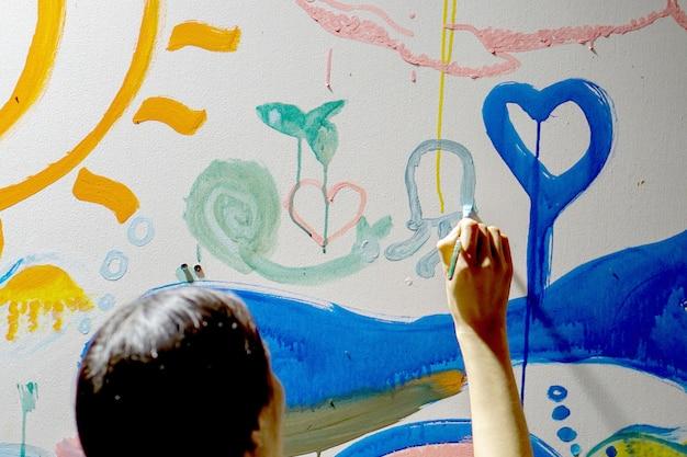 アジアの女の子が彼女の新しいアート教室の壁を描き、飾るのクローズアップと背面図 Premium写真