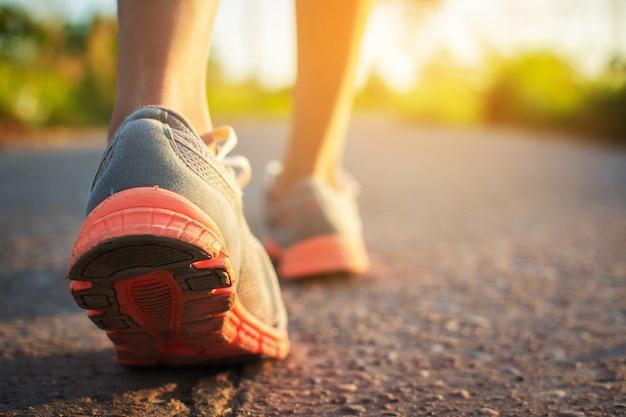 歩いている女性の足と日没時に道路上で運動します。 Premium写真
