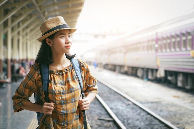 アジアの女性のバックパッキング鉄道駅、休日の概念の旅の旅を開始します。 Premium写真