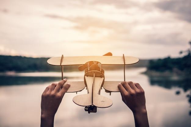 自然の中で木製の飛行機を持っている手 Premium写真