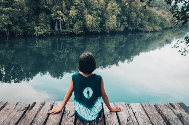 安静時と川を見ている木の板の上に座ってかわいい女の子 Premium写真