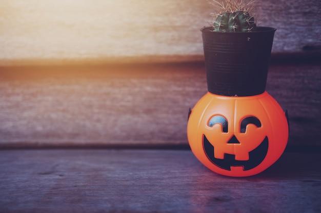 Кактус в черном горшке на хэллоуин тыква голову с золотым светом в темной ночи Premium Фотографии