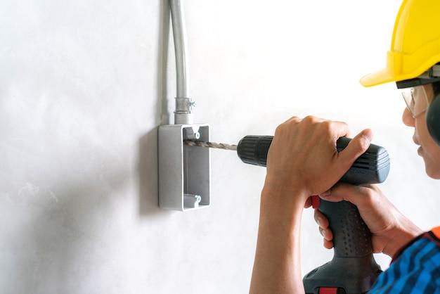 電気工事用ドリルドライバーを使用して住宅改修工事の電気接続箱に固定する Premium写真
