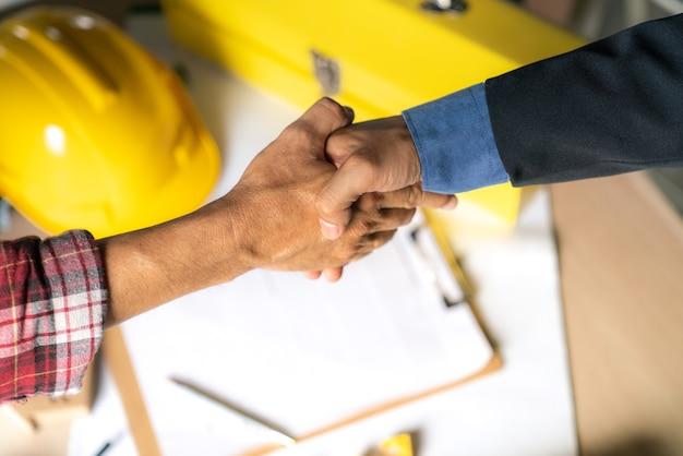 役員のチームワークは成功した家の建物の建設で祝うために幸せと手を振る Premium写真