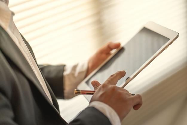 ビジネスマンは、会社の成功マーケティングプランに世界中のコミュニケーションの仕事のためにコンピューターのタブレットを使用します。 Premium写真