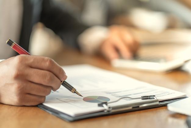 Бухгалтер проверяет документы о графике и диаграмме, относящиеся к финансовой отчетности и налоговому учету предприятия Premium Фотографии