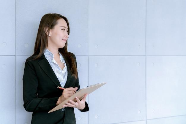 Азиатская красивая молодая бизнес-леди в юбке костюма используя рабочий документ о планах продаж и маркетинга Premium Фотографии