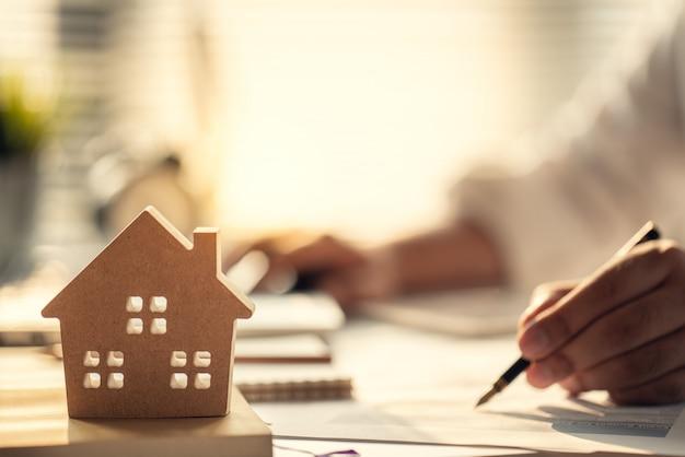 不動産や住宅購入に投資する利子、税金、利益を計算するビジネスマン Premium写真