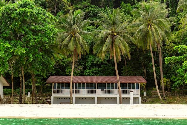 島の小さな別荘、そして小さな森の背景。 Premium写真