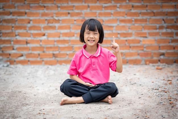 幸せな子供はレンガ壁の背景に地面に瞑想を座っています。 Premium写真