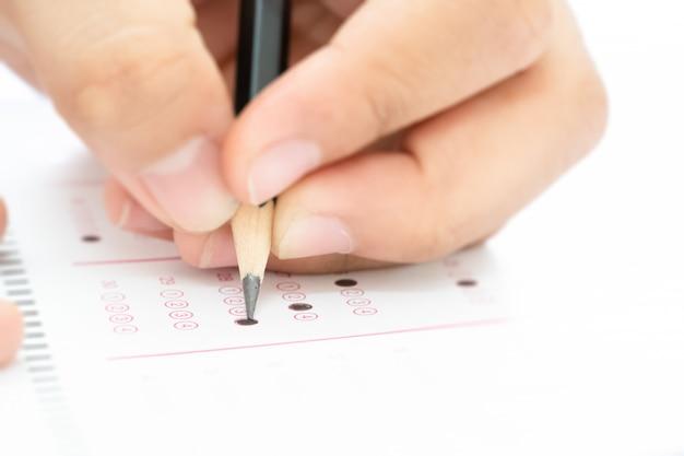 試験受験の答えを書いている手持ちの鉛筆 Premium写真