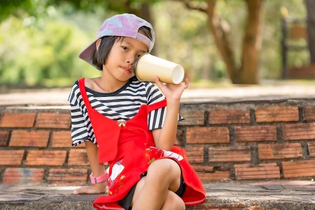 草原の牧草地の自然の屋外に紙コップから水を飲んで遊んで幸せな子供 Premium写真
