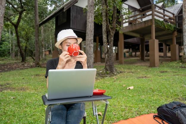 丘の自然に休暇の休日の時間にテーブルでコーヒーを飲む女の子 Premium写真