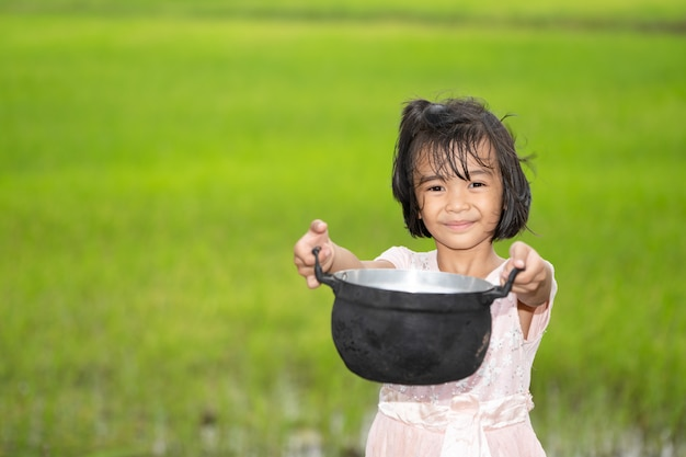 朝はぼやけ緑の田んぼにフードポットを保持している子供 Premium写真