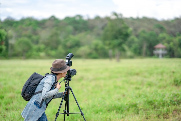 女性カメラマンが丘の自然で写真を撮る Premium写真