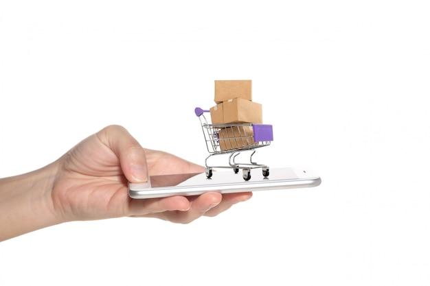 トロリーの紙箱とスマートフォンを持つ女性の手。 Premium写真