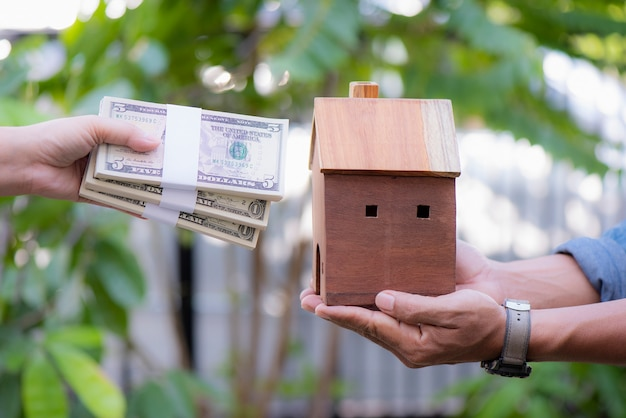 Кредиты для концепции недвижимости рука деньги и модель дома вместе в общественном парке Premium Фотографии