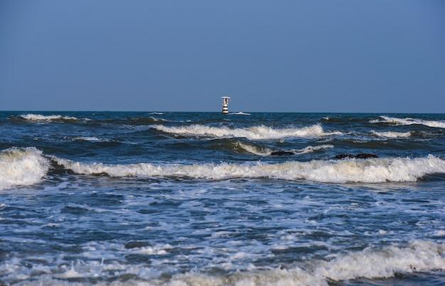灯台タワーは澄んだ青い日に海の真ん中にあります。 Premium写真