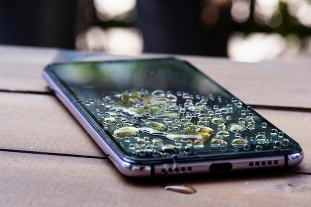 スマートフォンにこぼれた水モバイルの画面に水が一滴 Premium写真