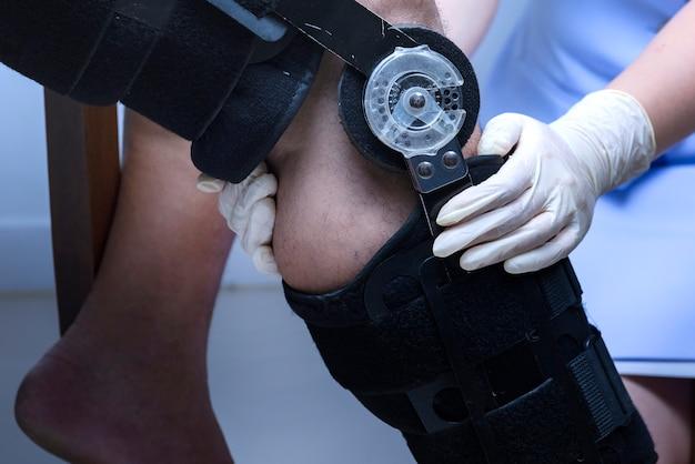 整形外科医は膝の上に脚部ブレースを固定、膝のブレース Premium写真