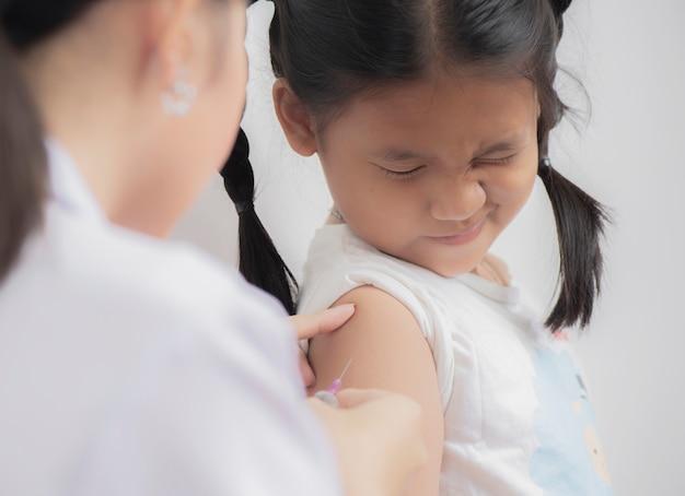 医者の小さな子供の女の子の腕に予防接種を注入 Premium写真