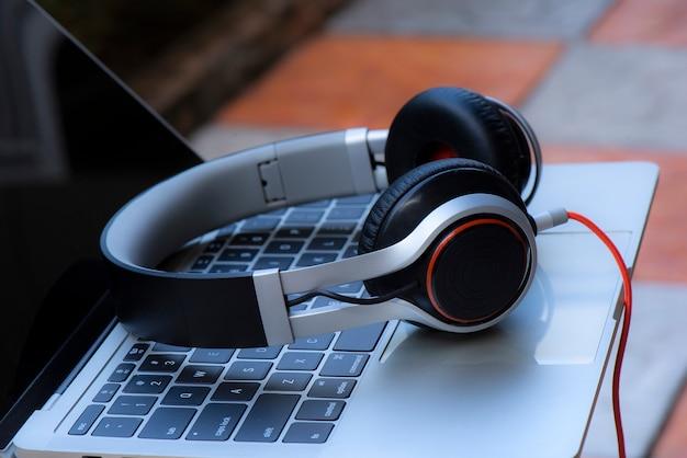 Наушники и ноутбук на белом столе с расфокусированным фоном Premium Фотографии