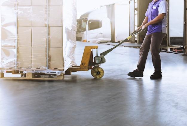 ロジスティックと倉庫。荷物と共にパレットトラックをドラッグするトラック運転手 Premium写真