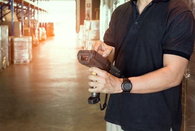 倉庫作業員は倉庫内の商品を在庫したバーコードスキャナーを持っています。 Premium写真