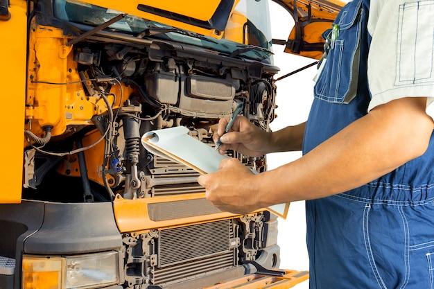 トラックのエンジンを検査する自動車整備士持株クリップボード。 Premium写真