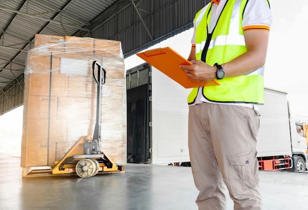 トラックに積み込む貨物の詳細を検査するクリップボードを持っている倉庫作業員の手 Premium写真
