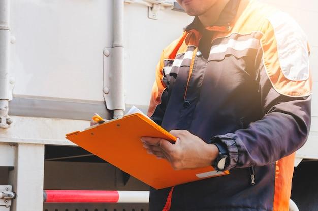 輸送する詳細出荷を検査するクリップボードを持っている労働者の手 Premium写真