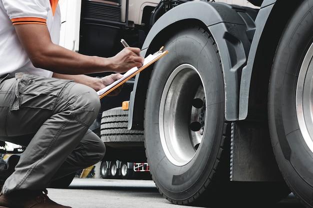 Водитель грузовика осматривает детали контрольного перечня безопасности грузовых шин. Premium Фотографии