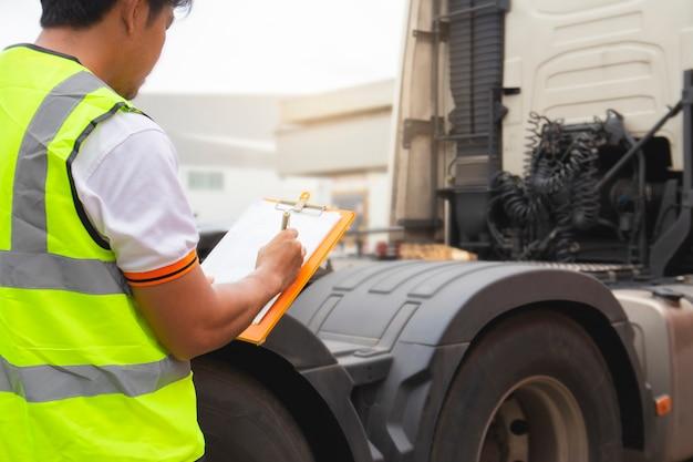 毎日の安全をチェックするトラック運転手がセミトラックをチェックリスト Premium写真