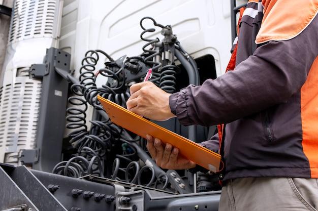 セミトラックの安全車両保守チェックリストを検査するクリップボードを保持しているトラック運転手 Premium写真