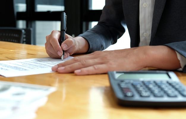 ビジネスマンはオフィスで契約書に署名しています。 Premium写真