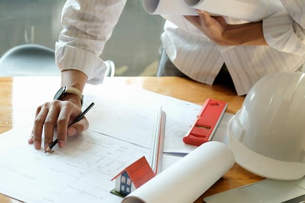 デザイナーは家をデザインしています。モデル住宅とテーブルの上の住宅計画。 Premium写真