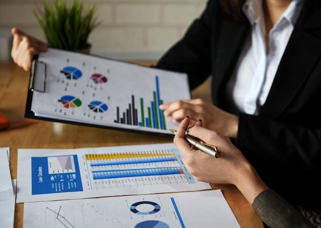 ビジネスコンセプトを立ち上げ、新しいオフィスのスタッフはグラフからデータを分析しています。 Premium写真