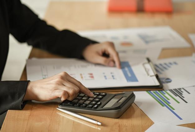 Женщины-предприниматели используют калькулятор, ручку, чтобы спланировать маркетинговый план по улучшению качества. Premium Фотографии
