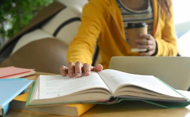 学生は本を読んで、試験の準備のためにメモを取っています。 Premium写真