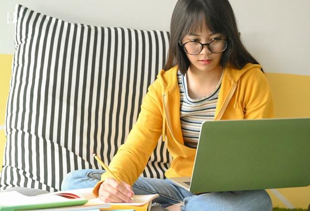眼鏡をかけているアジアの女子学生がラップトップで調査し、レポートを作成するためにメモを取っています。 Premium写真