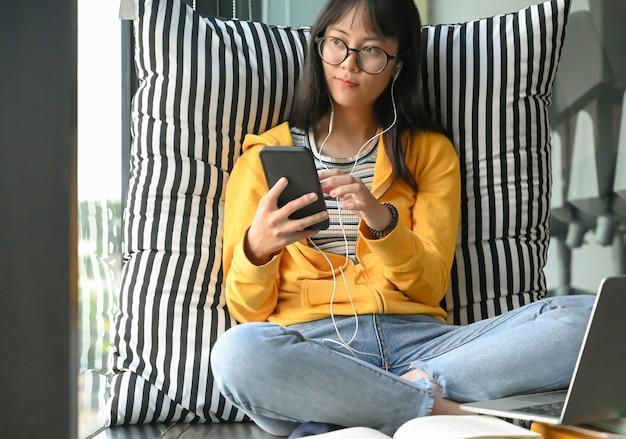 アジアの女子学生が眼鏡をかけて、スマートフォンやヘッドフォンから音楽を聴きます。 Premium写真